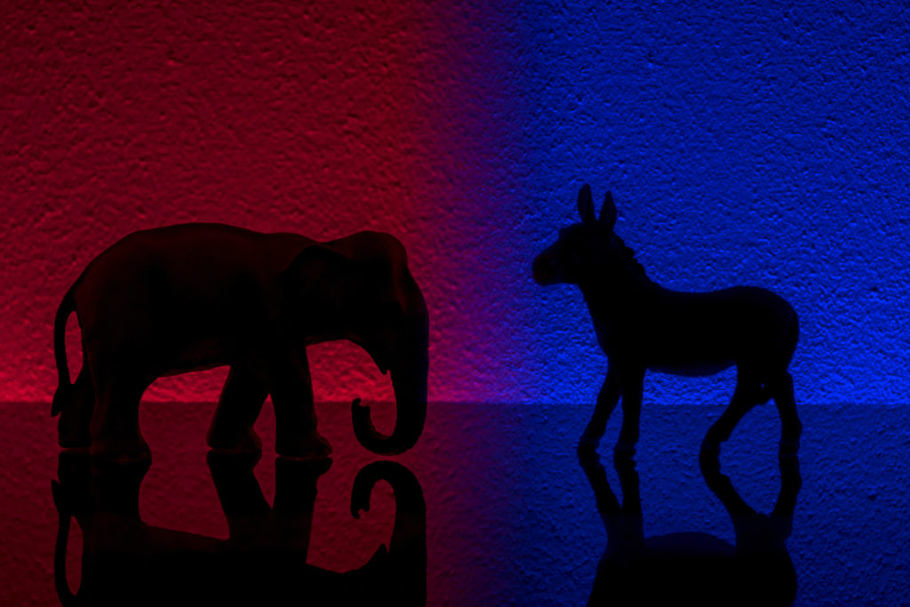 Democrats vs republicans are facing off in a ideological duel on blue and red backgrounds.